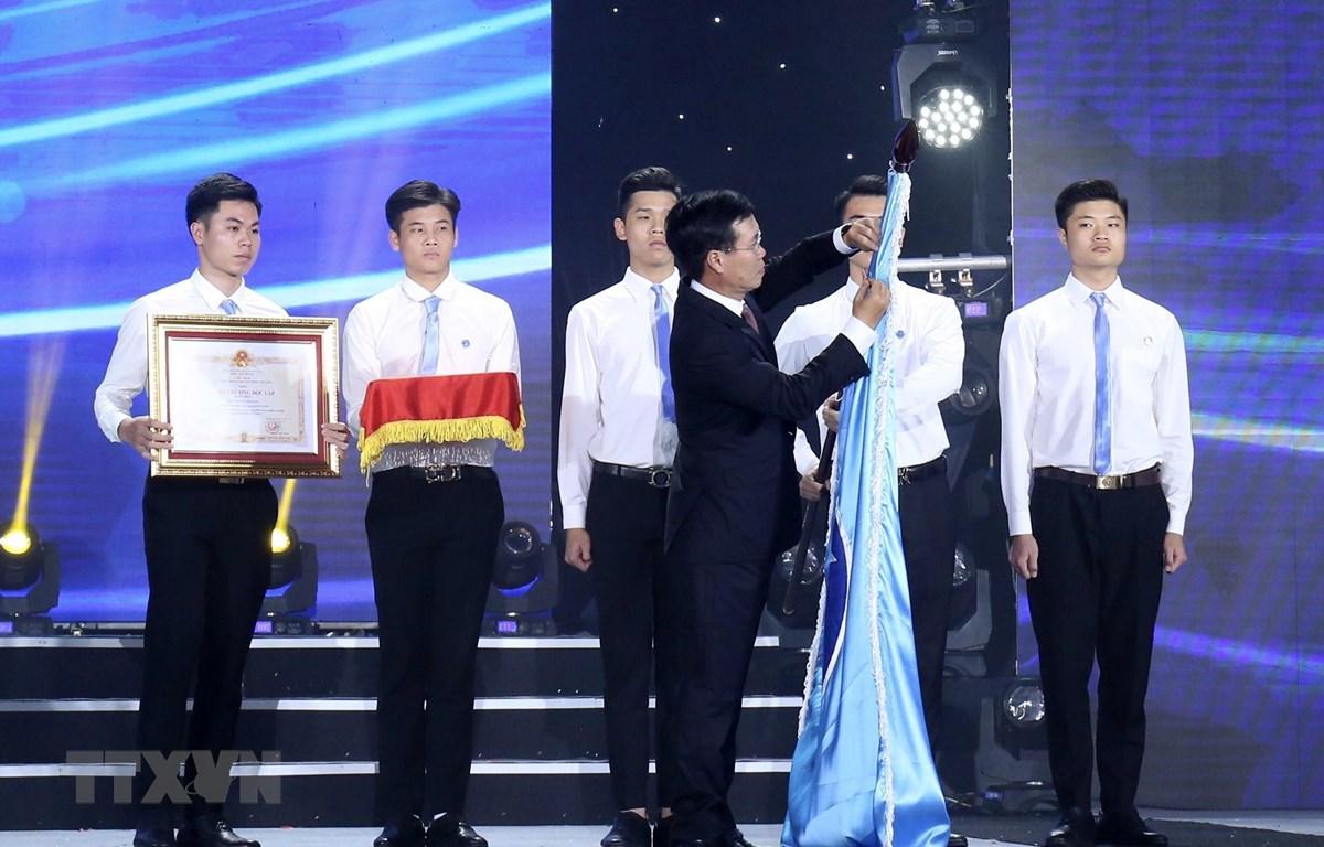 Trưởng Ban Tuyên giáo Trung ương Võ Văn Thưởng gắn Huân chương Độc lập hạng Nhất (lần thứ II) của Chủ tịch nước lên lá cờ của Hội Sinh viên Việt Nam. (Ảnh: Văn Điệp/TTXVN)
