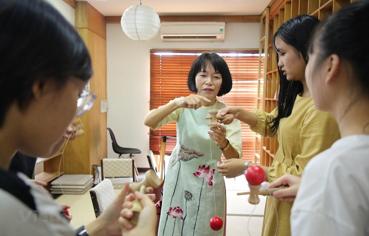 Cô Shuto Mika hướng dẫn sinh viên tập trò chơi truyền thống Nhật Bản. (Ảnh: Minh Sơn/Vietnam+)