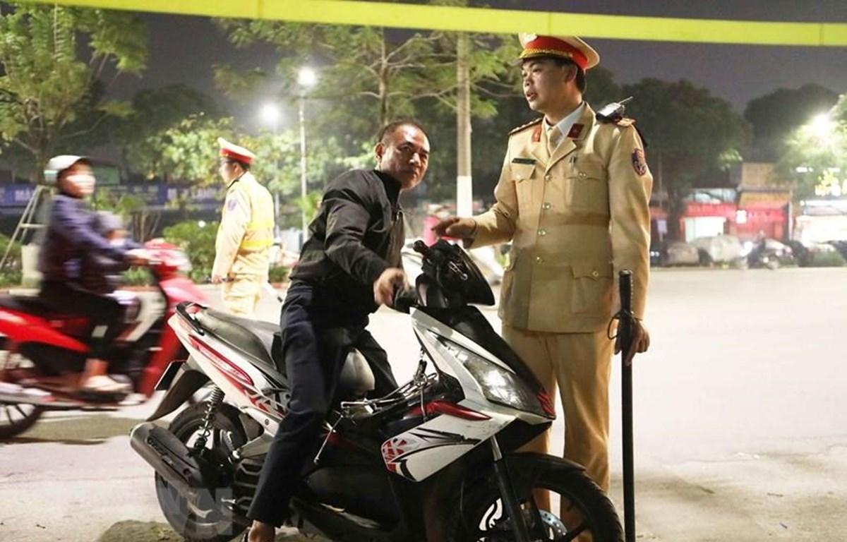 Một trường hợp không đội mũ bảo hiểm khi đi xe máy bị cảnh sát yêu cầu dừng xe để xử lý vi phạm. (Ảnh: Doãn Tấn/TTXVN)