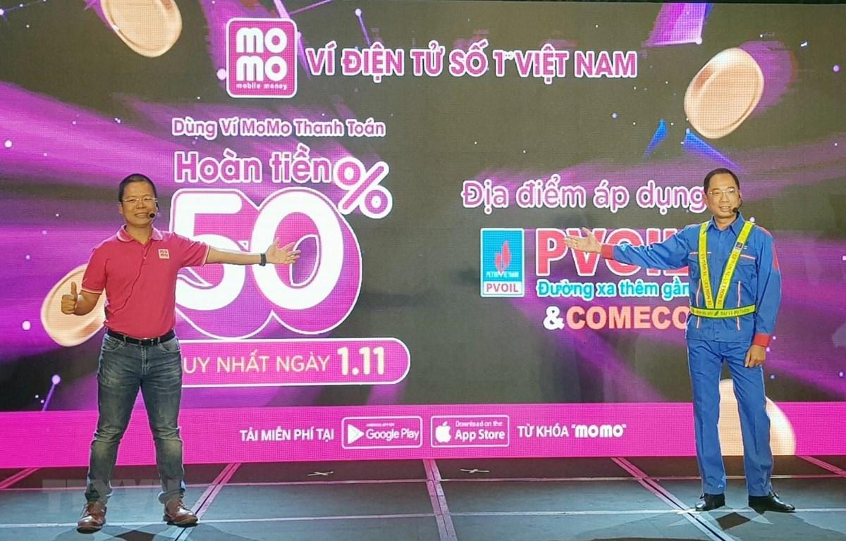 Đại diện PVOIL và Ví MoMo phát động thí điểm ứng dụng thanh toán bằng ví điện tử tại cửa hàng xăng dầu. (Ảnh: Mỹ Phương/TTXVN)