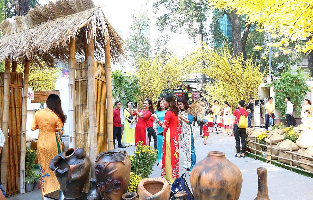 Các bạn trẻ chụp ảnh tại Lễ hội Tết Việt với nét mộc mạc của làng quê, hay một góc Sài Gòn xưa. (Ảnh: Thanh Vũ - TTXVN)