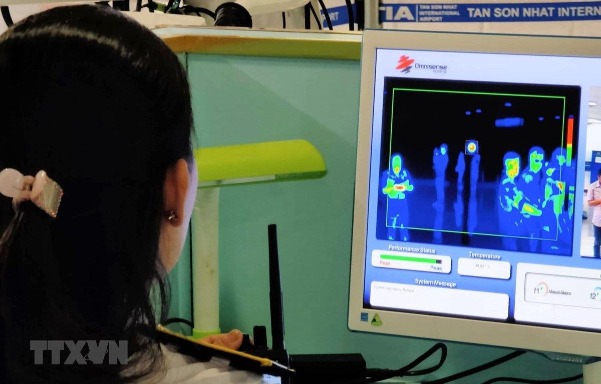 Nhân viên sân bay Tân Sơn Nhất kiểm tra màn hình hiển thị máy quét thân nhiệt đối với hành khách quốc tế đến Việt Nam. (Ảnh: Đinh Hằng/TTXVN)