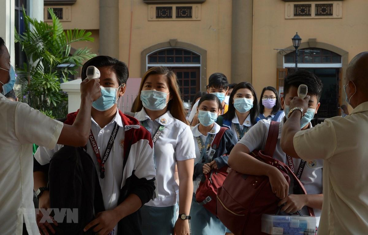 Các sinh viên đeo khẩu trang và được kiểm tra thân nhiệt phòng tránh lây nhiễm virus corona tại một trường học ở Malina, Philippines,ngày 31/1/2020. (Ảnh: AFP/TTXVN)