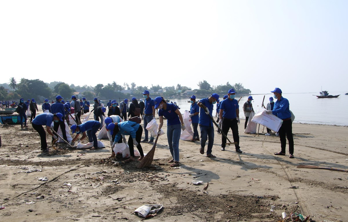 Các đoàn viên thanh niên dọn rác thải nhựa tại bãi biển thôn An Vĩnh, Quảng Ngãi. (Ảnh: Đinh Hương/TTXVN)