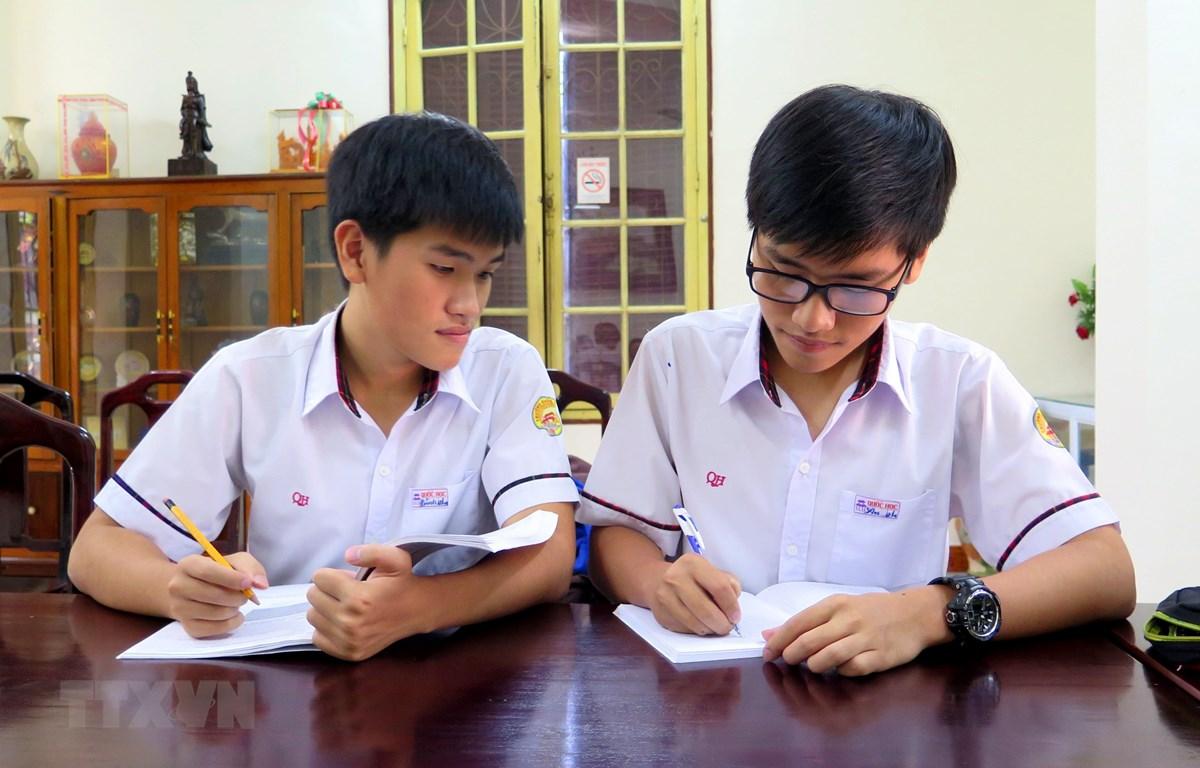 Hai anh em Tống Phước Thanh Bình và Tống Phước Thanh An (người đeo kính) trao đổi bài trước giờ lên lớp. (Ảnh: Tường Vi/TTXVN)