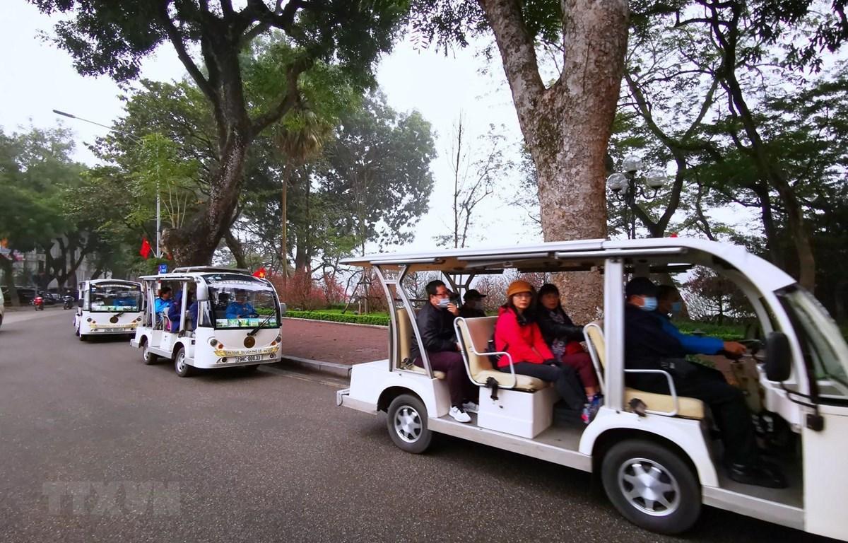 Khách du lịch tham quan hồ Hoàn Kiếm bằng xe điện. (Ảnh: Thành Đạt/ TTXVN)