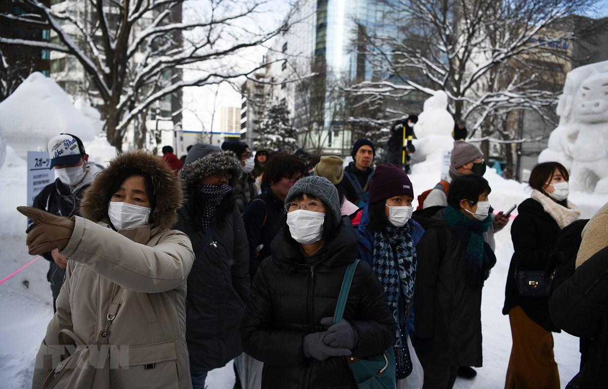 Khách du lịch đeo khẩu trang đề phòng lây nhiễm dịch COVID-19 khi tham quan lễ hội tuyết thường niên tại thành phố Sapporo, Nhật Bản ngày 4/2/2020. (Ảnh: AFP/TTXVN)