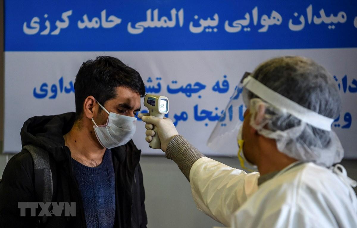 Nhân viên y tế kiểm tra thân nhiệt cho hành khách tại sân bay quốc tế Hamid Karzai ở thủ đô Kabul, Afghanistan ngày 2/2/2020. (Ảnh: AFP/TTXVN)