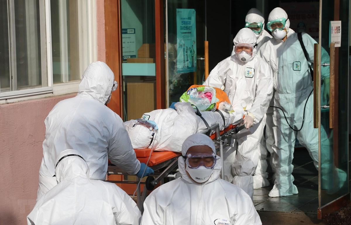 Nhân viên y tế Hàn Quốc chuyển bệnh nhân nhiễm COVID-19 từ một bệnh viện ở Cheongdo đến một bệnh viện khác để điều trị ngày 21/2/2020. (Ảnh: Yonhap/TTXVN)