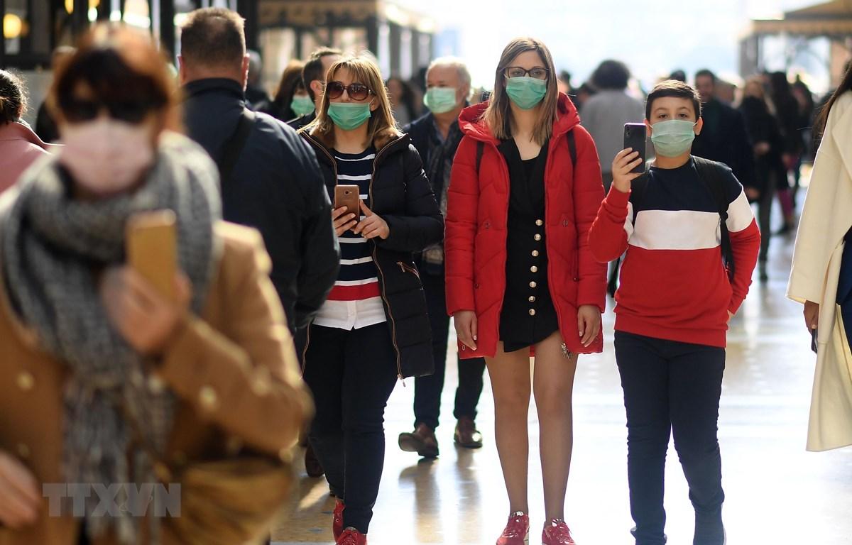 Người dân đeo khẩu trang để phòng tránh lây nhiễm COVID-19 tại Milan, Italy, ngày 24/2/2020. (Ảnh: THX/TTXVN)