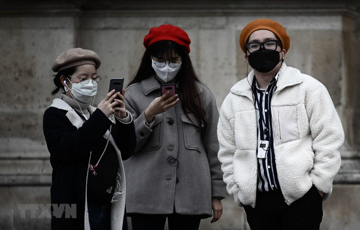 Du khách đeo khẩu trang đề phòng lây nhiễm COVID-19 tại Paris, Pháp ngày 31/1/2020. (Ảnh: AFP/TTXVN)