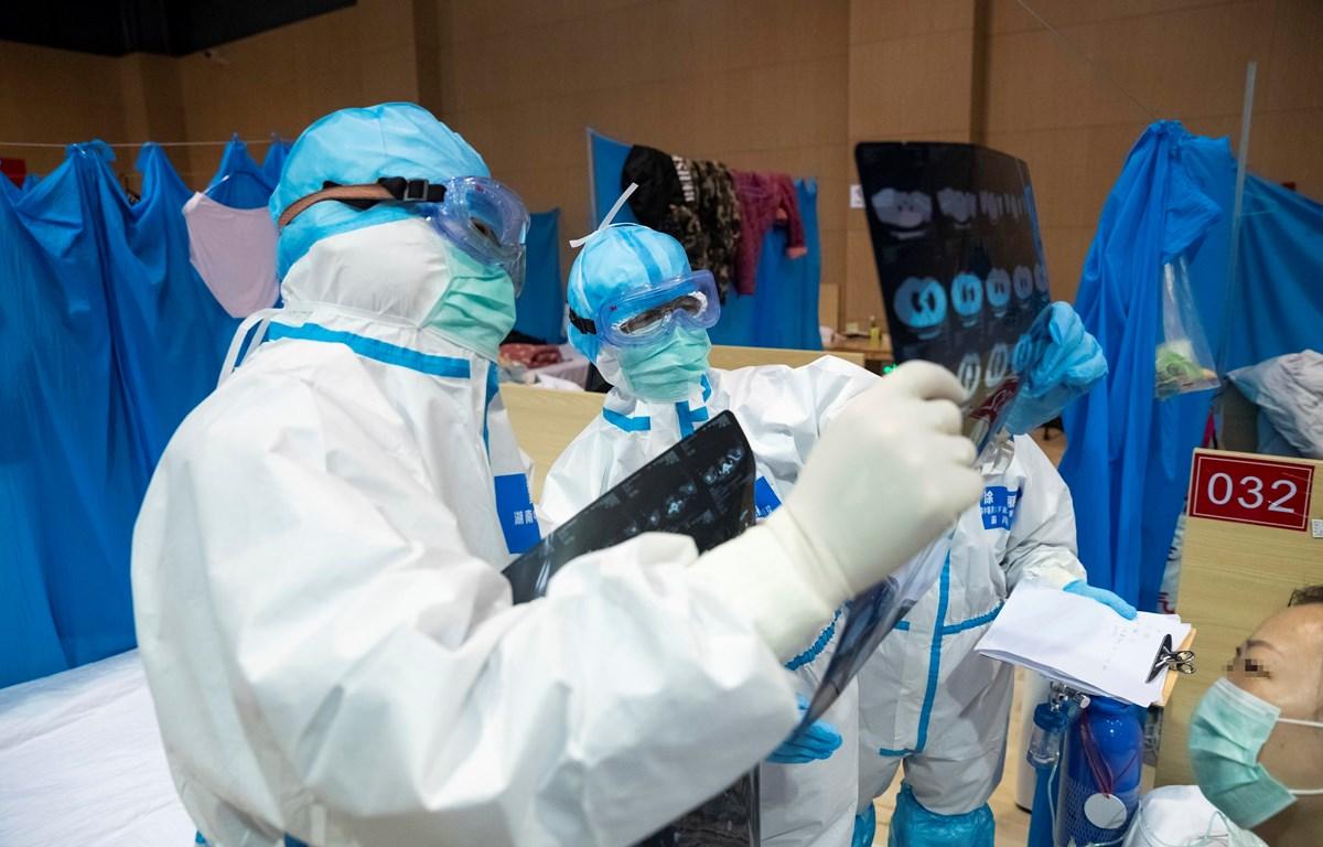 Nhân viên y tế kiểm tra phim chụp CT của bệnh nhân nhiễm COVID-19 tại bệnh viện dã chiến ở Vũ Hán, tỉnh Hồ Bắc, Trung Quốc, ngày 25/2/2020. (Ảnh: THX/TTXVN)