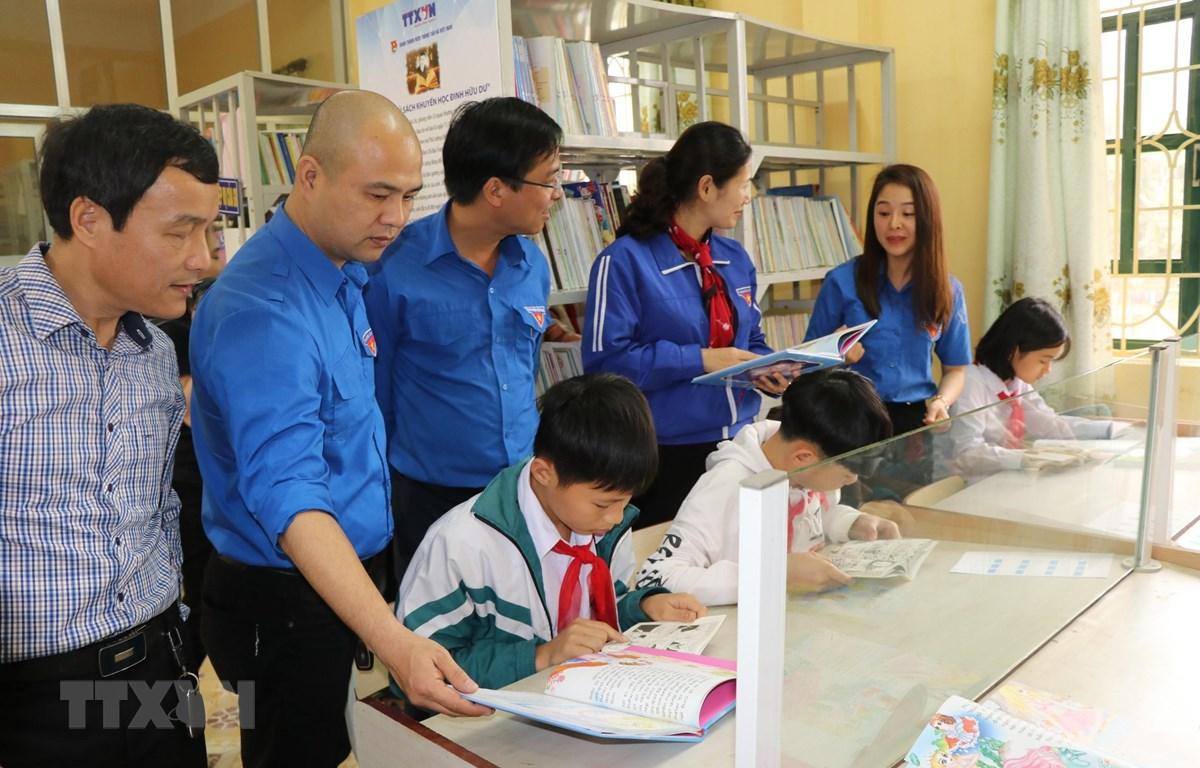 Đại diện Đoàn Thanh niên Thông tấn xã Việt Nam và Tỉnh đoàn Yên Bái giới thiệu các đầu sách cho các em học sinh. (Ảnh: Đinh Thùy-TTXVN)