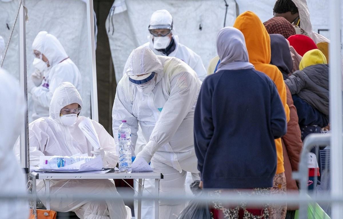 Nhân viên Hội Chữ thập đỏ Italy trong trang phục bảo hộ chống virus SARS-CoV-2 khi tiếp nhận người di cư được giải cứu trên Địa Trung Hải tại khu cảng ở Messina, Sicily ngày 27/2/2020. (Ảnh: AFP/TTXVN)