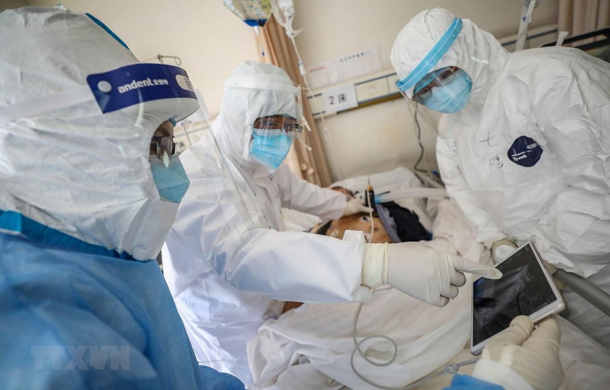 Nhân viên y tế điều trị cho bệnh nhân nhiễm COVID-19 tại bệnh viện ở Vũ Hán, Trung Quốc, ngày 16/2. (Ảnh: AFP/TTXVN)