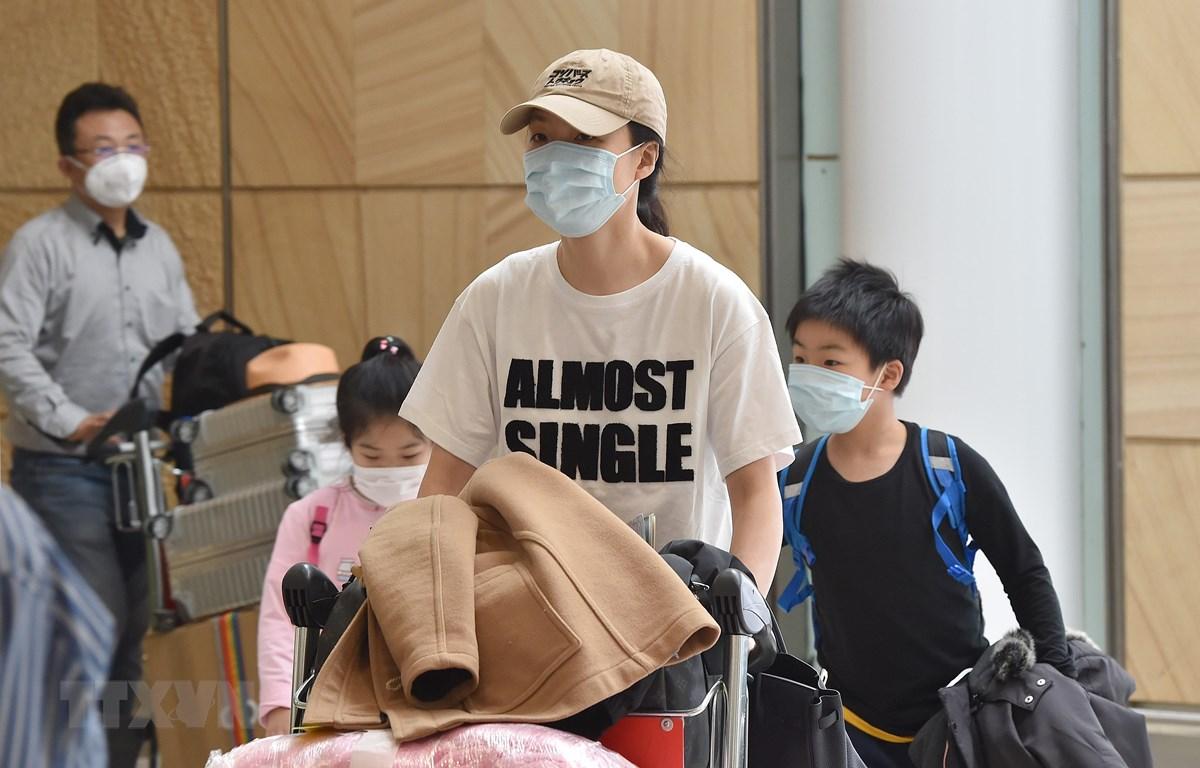 Hành khách đeo khẩu trang phòng tránh lây nhiễm virus corona tại sân bay Sydney, Australia. (Ảnh: AFP/TTXVN)