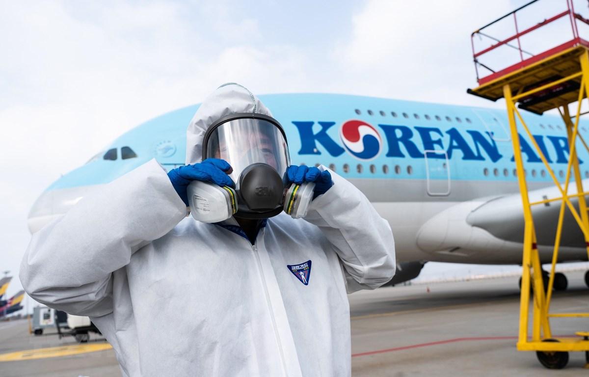 Nhân viên chuẩn bị phun thuốc khử trùng trên máy bay của Korean Air nhằm ngăn chặn sự lây lan của dịch COVID-19 tại sân bay quốc tế Incheon, Hàn Quốc, ngày 4/3. (Ảnh: AFP/TTXVN)