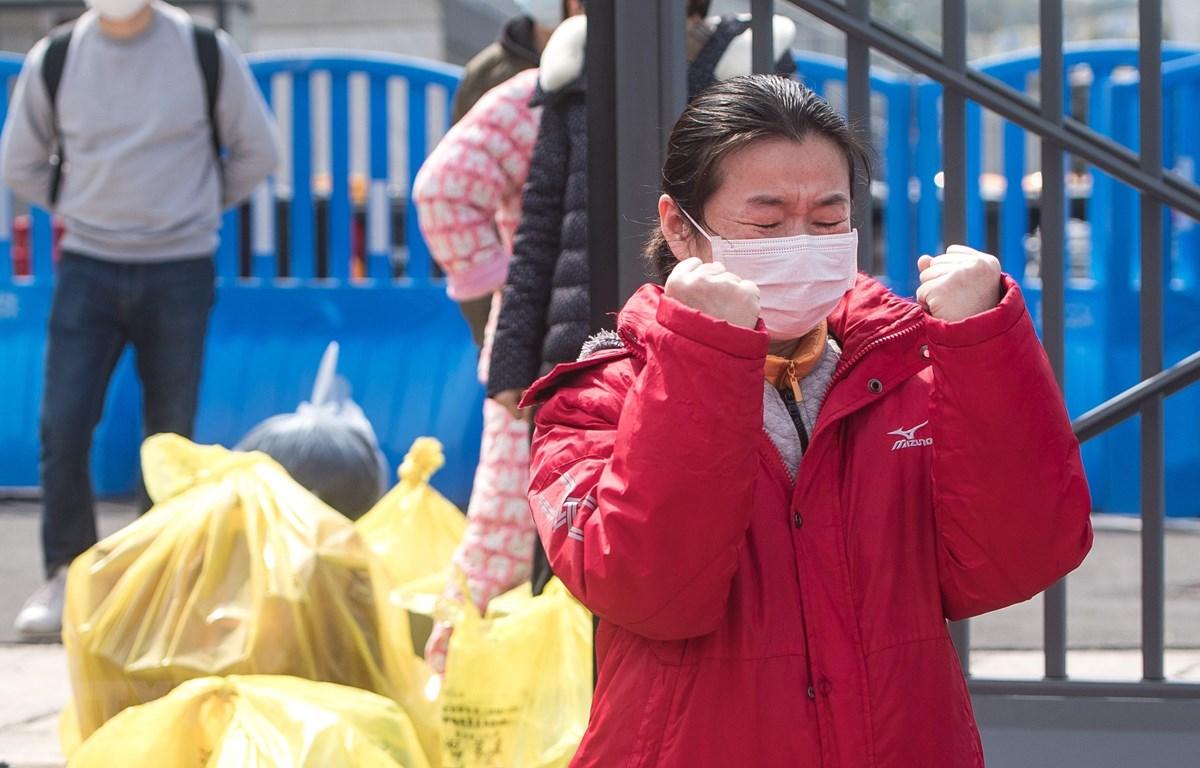 Một bệnh nhân được điều trị khỏi COVID-19 xúc động khi rời bệnh viện dã chiến ở Vũ Hán, tỉnh Hồ Bắc, Trung Quốc, ngày 8/3/2020, trước khi bệnh viện này đóng cửa. (Ảnh: THX/TTXVN)