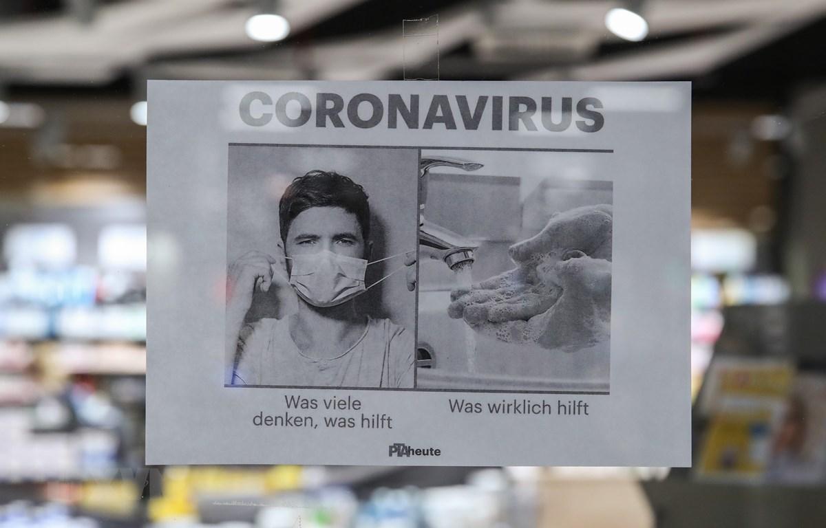 Tấm biển kêu gọi người dân rửa tay thường xuyên và đeo khẩu trang để phòng tránh lây nhiễm COVID-19, tại một hiệu thuốc ở Berlin, Đức (Ảnh: THX/TTXVN)