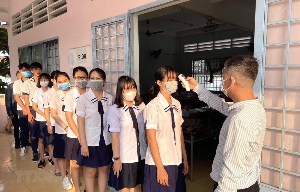 Trường THPT Vĩnh Long (thành phố Vĩnh Long, Việt Nam) đo thân nhiệt cho học sinh ngày 2/3. (Ảnh: Lê Thúy Hằng/TTXVN)