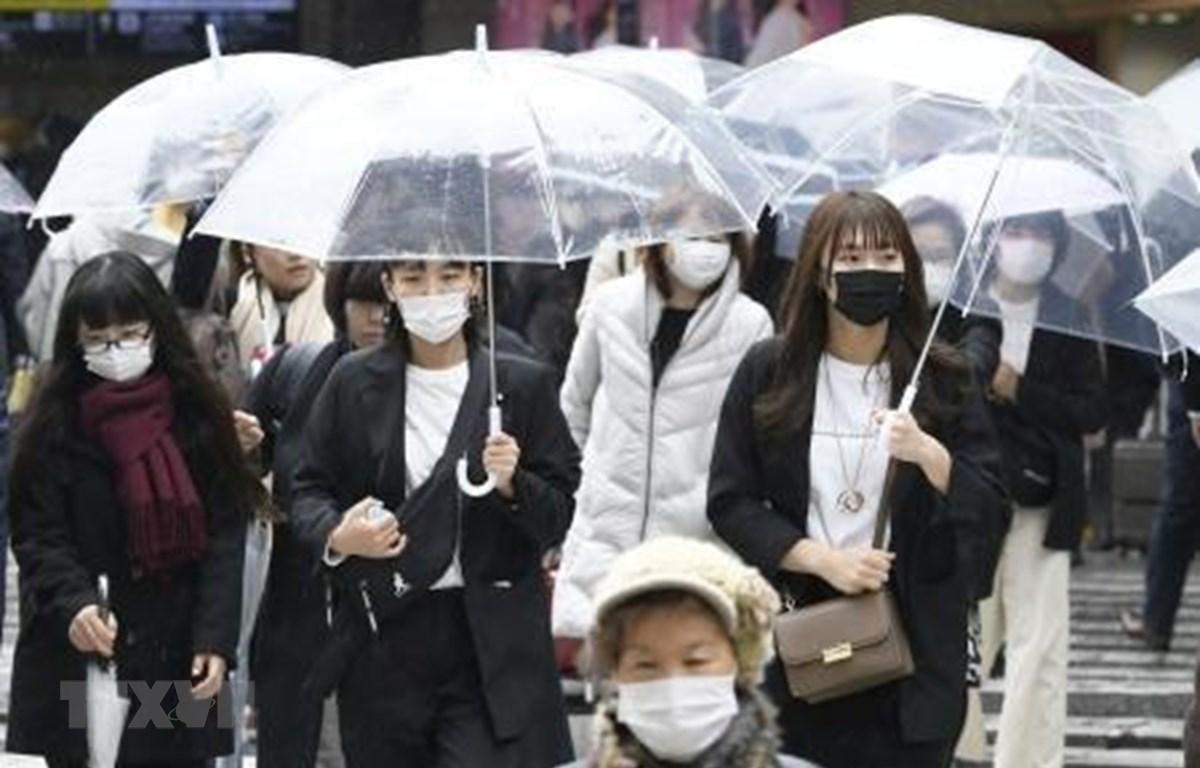 Người dân đeo khẩu trang phòng tránh COVID-19 tại Osaka, Nhật Bản. (Ảnh: Kyodo/TTXVN)