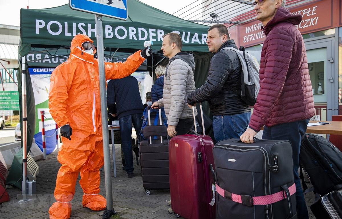 Nhân viên y tế kiểm tra thân nhiệt hành khách đi qua cửa khẩu biên giới Đức-Ba Lan, từ thị trấn Frankfurt tới Slubice nhằm ngăn ngừa dịch COVID-19 lây lan, ngày 16/3/2020. (Ảnh: AFP/TTXVN)