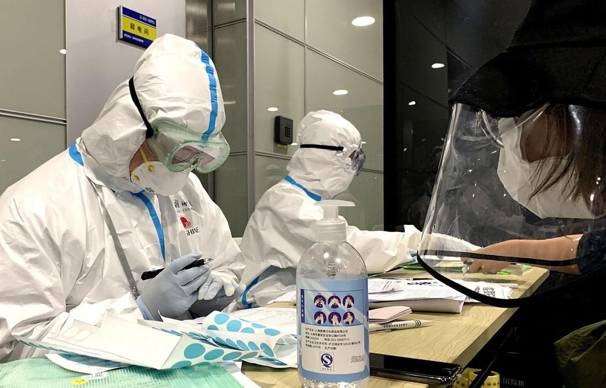 Nhân viên y tế cung cấp thông tin về dịch COVID-19 tại sân bay quốc tế ở Thượng Hải, Trung Quốc, ngày 15/3/2020. (Ảnh: THX/TTXVN)