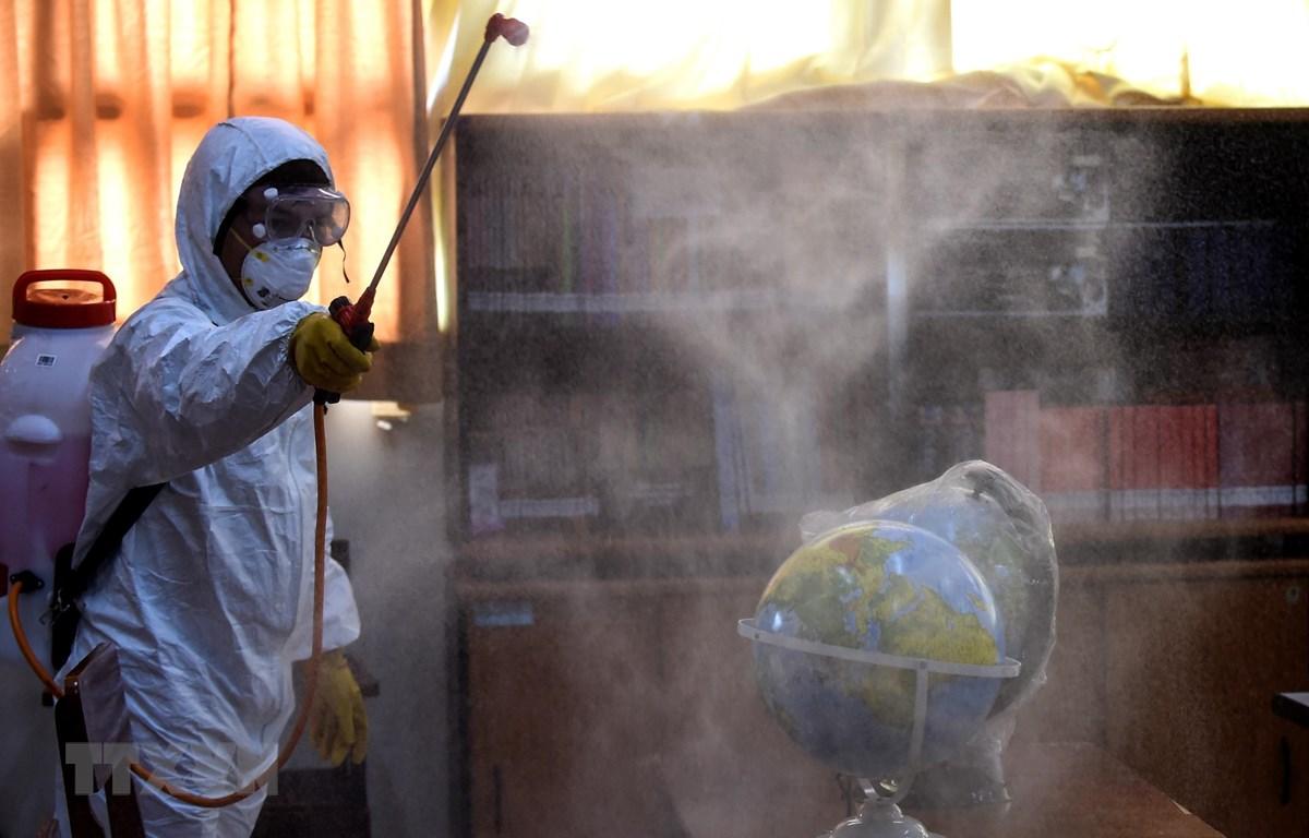 Nhân viên hội Chữ thập đỏ phun thuốc khử trùng tại trường học ở Jakarta, Indonesia ngày 20/3/2020, nhằm ngăn chặn sự lây lan của COVID-19. (Ảnh: THX/TTXVN)