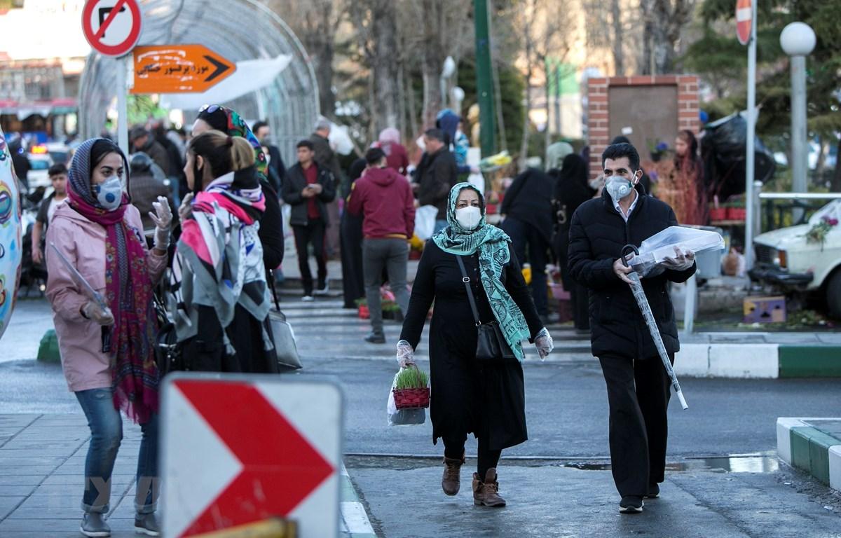 Người dân đeo khẩu trang để phòng tránh lây nhiễm COVID-19 tại Tehran, Iran, ngày 19/3/2020. (Ảnh: THX/TTXVN)