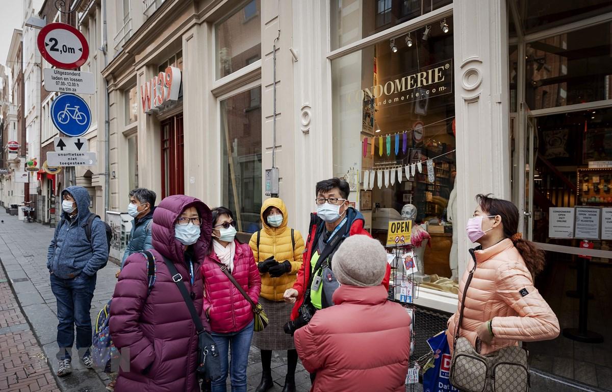 Người dân đeo khẩu trang nhằm ngăn chặn sự lây lan của dịch COVID-19 tại Amsterdam, Hà Lan ngày 17/3/2020. (Ảnh: AFP/TTXVN)