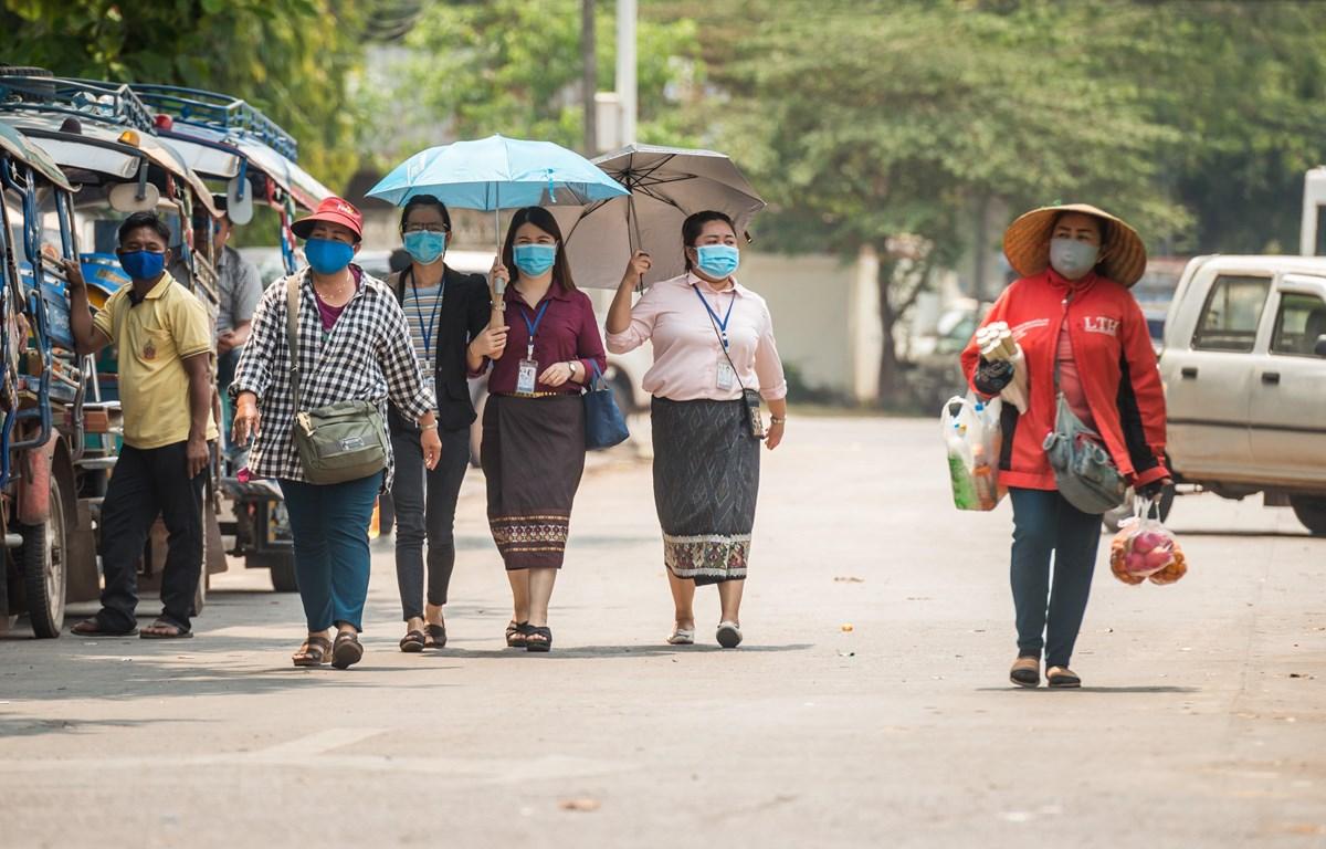 Người dân đeo khẩu trang nhằm ngăn chặn sự lây lan của dịch COVID-19 tại thủ đô Vientiane, Lào ngày 23/3/2020. (Ảnh: THX/TTXVN)