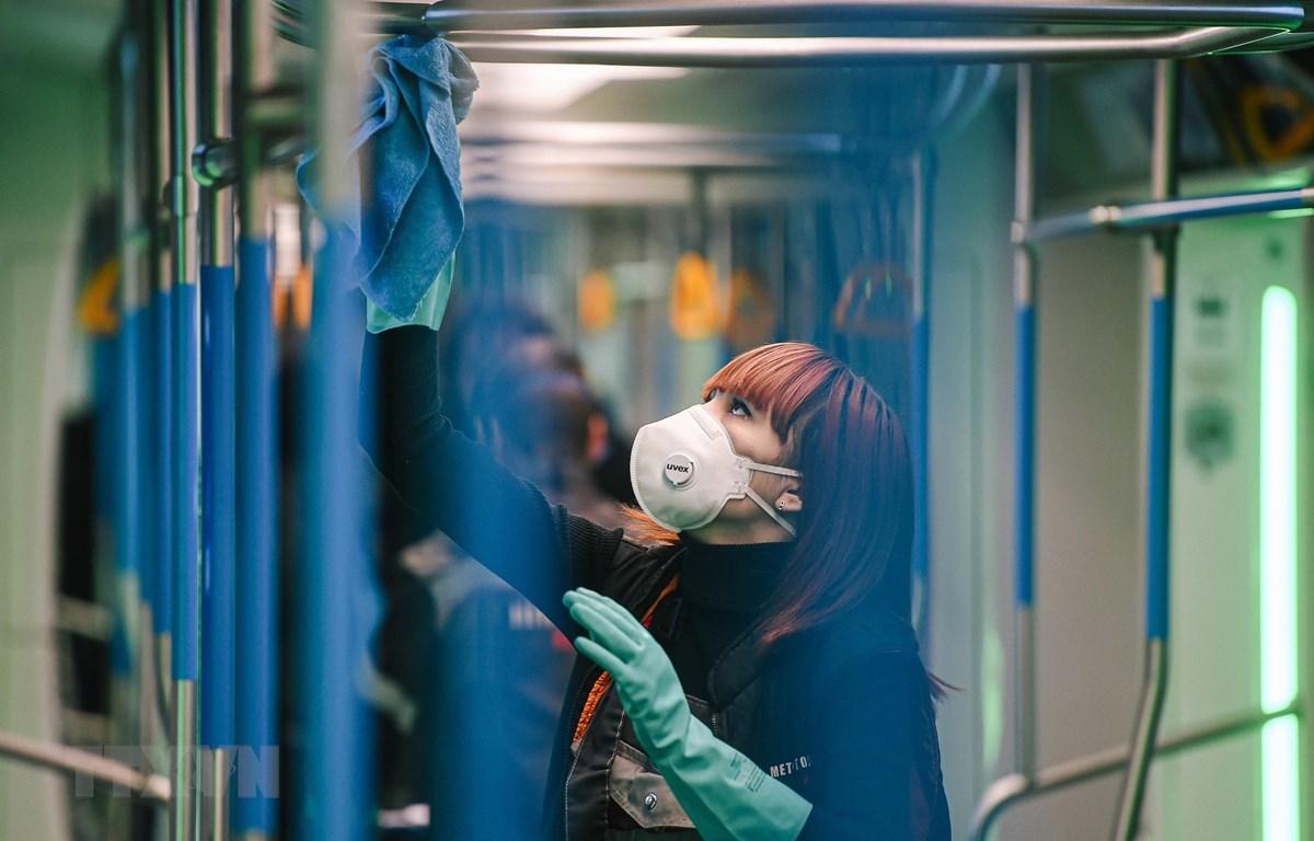 Nhân viên phun thuốc khử trùng trên tàu điện ngầm tại Moskva, Nga ngày 16/3/2020, nhằm ngăn chặn sự lây lan của COVID-19. (Ảnh: THX/TTXVN)