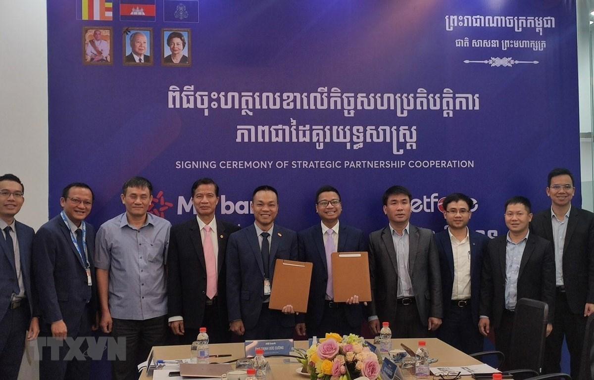 Lãnh đạo Công ty Viettel Cambodia (Metfone) thuộc Tập đoàn Viettel và Chi nhánh của Ngân hàng Quân đội (MB Cambodia) ký Bản ghi nhớ Hợp tác chiến lược. (Ảnh: Nguyễn Vũ Hùng/TTXVN)