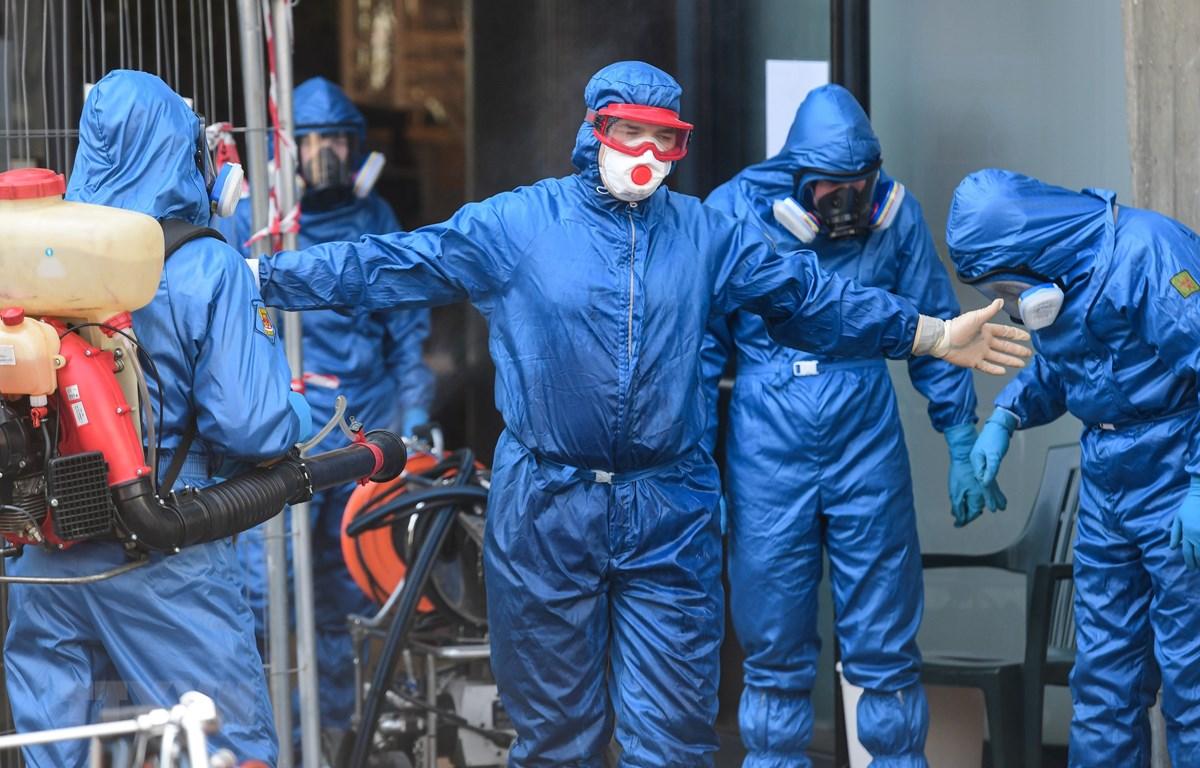 Chuyên gia quân đội Nga khử khuẩn bên ngoài Viện dưỡng lão ở Albino, Italy, nơi có 35 trường hợp tử vong do dịch COVID-19, ngày 28/3/2020. (Ảnh: AFP/TTXVN)