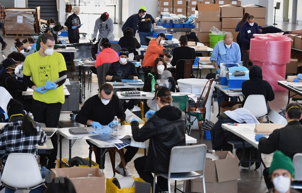 Sản xuất mặt nạ phòng hộ ngăn virus gây dịch COVID-19 cho nhân viên y tế tại Công ty chế tạo thiết bị công nghiệp PPE ở New York, Mỹ ngày 26/3/2020. (Ảnh: AFP/TTXVN)
