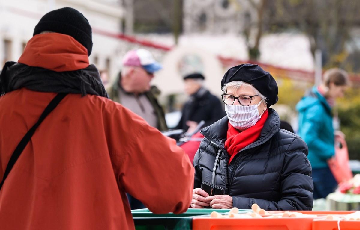 Người dân đeo khẩu trang để phòng tránh lây nhiễm COVID-19 khi mua sắm tại chợ ở Leipzig, Đức ngày 4/4/2020. (Ảnh: THX/ TTXVN)