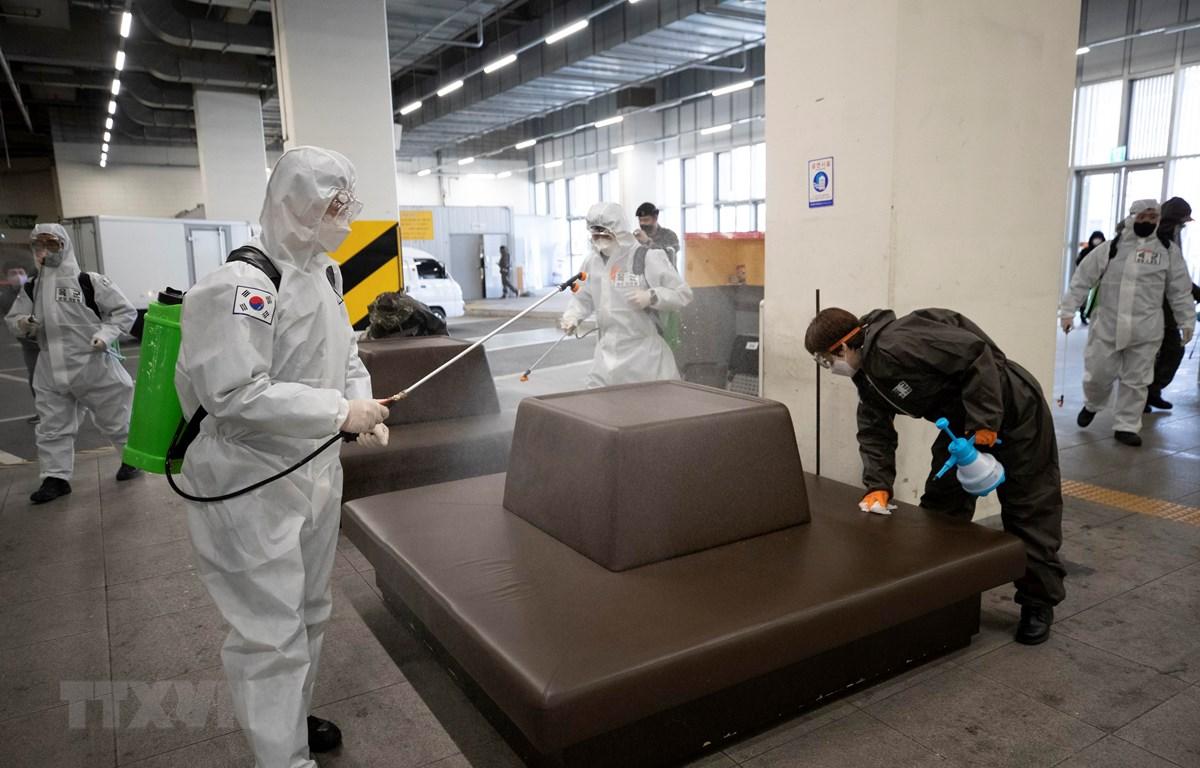 Phun thuốc khử trùng tại một trạm xe buýt ở Daegu, Hàn Quốc, nhằm ngăn chặn sự lây lan của dịch COVID-19, ngày 14/3/2020. (Ảnh: Yonhap/ TTXVN)