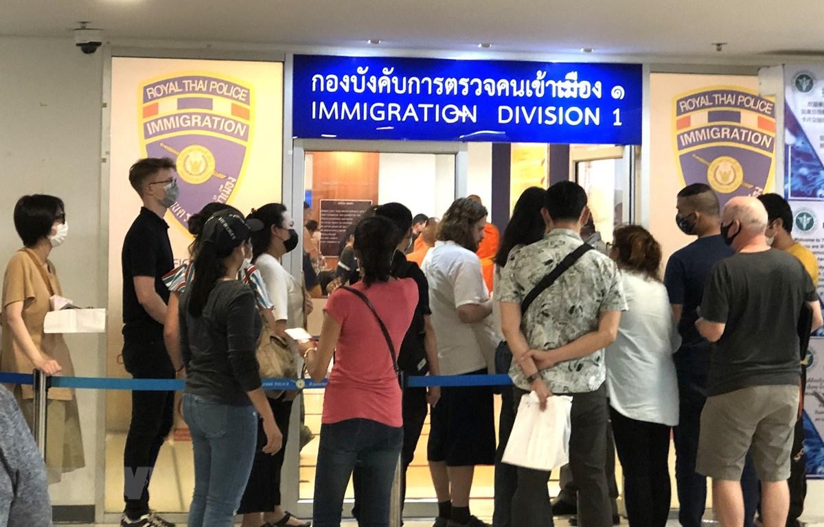 Nhiều người nước ngoài xếp hàng bên ngoài văn phòng Cục Di trú Thái Lan ở Bangkok để xin gia hạn thị thực nhập cảnh ngày 23/3. (Ảnh: Ngọc Quang/TTXVN)