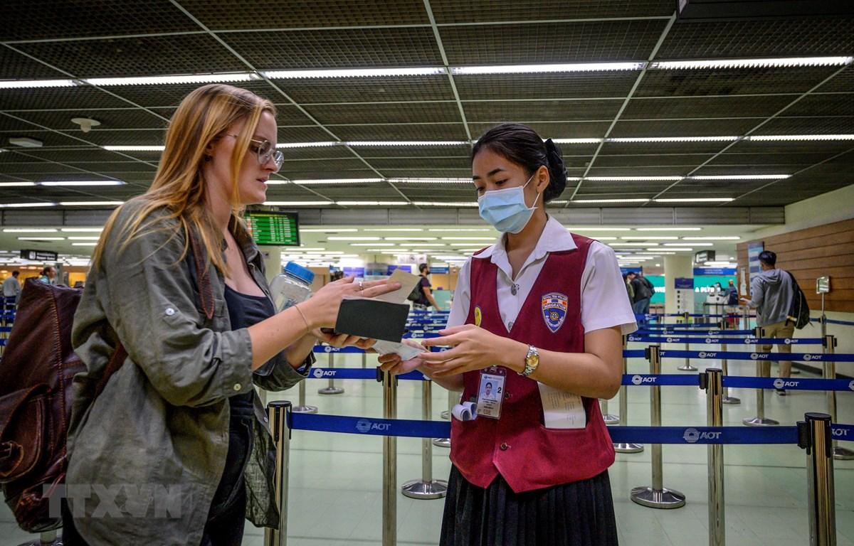 Nhân viên sân bay kiểm tra hộ chiếu của một hành khách tại sân bay Don Mueang ở Bangkok, Thái Lan ngày 21/1/2020. (Ảnh: AFP/TTXVN)