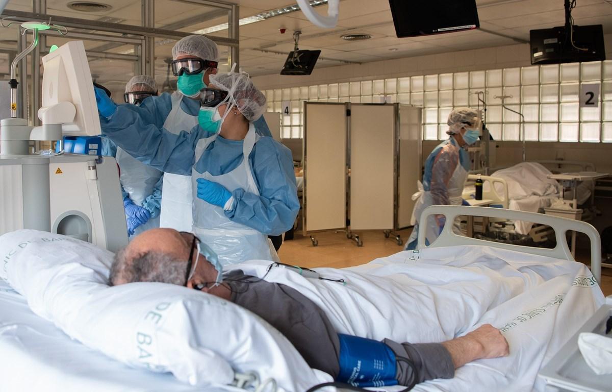 Nhân viên y tế điều trị cho bệnh nhân mắc COVID-19 tại một bệnh viện ở Barcelona, Tây Ban Nha ngày 7/4/2020. (Ảnh: THX/TTXVN)