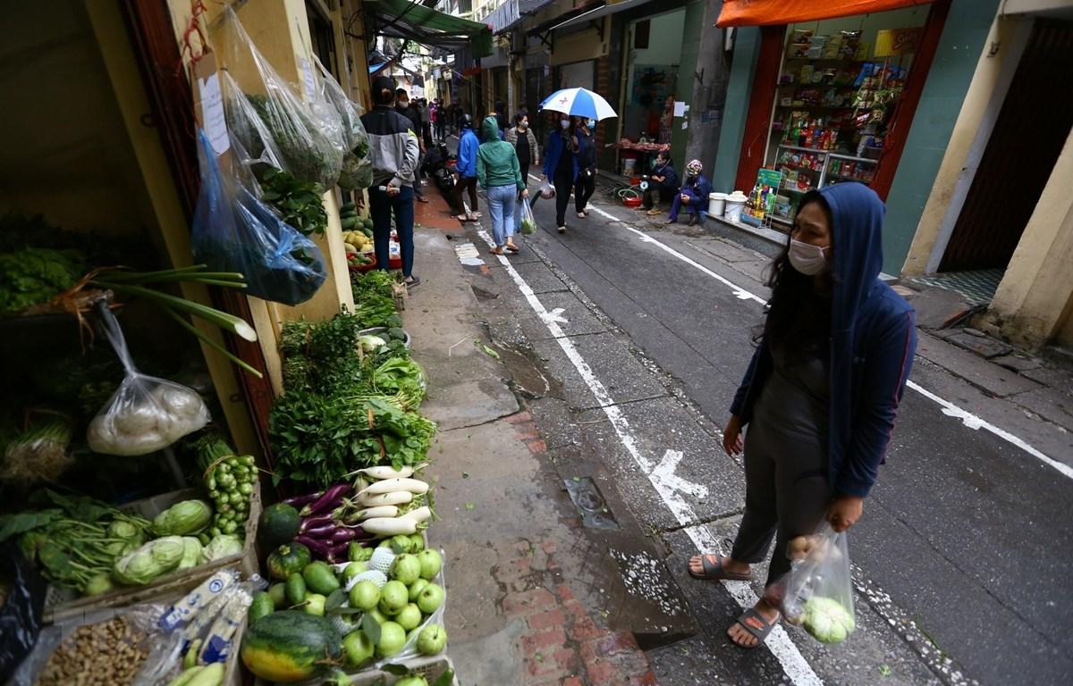 Tại những khu chợ dân sinh ở Hà Nội, đường phố được kẻ vạch sơn, quy định khoảng cách giữa người mua và người bán. (Ảnh: Minh Quyết - TTXVN)