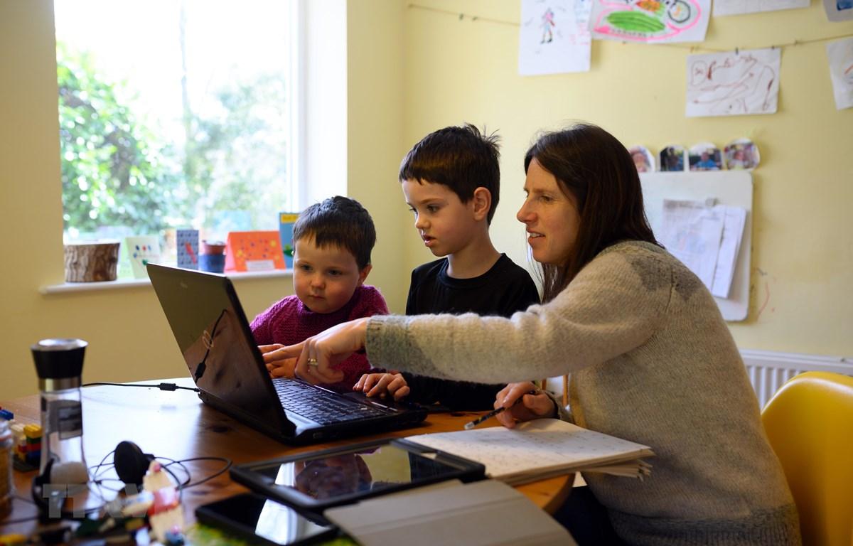 Một gia đình ở Anh giúp con học trực tuyến do các trường học phải đóng cửa vì dịch COVID-19. (Ảnh: AFP/TTXVN)