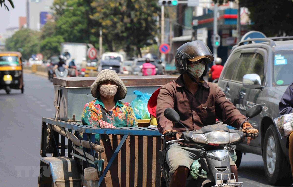 Người dân đeo khẩu trang phòng lây nhiễm COVID-19 trên một đường phố ở Phnom Penh, Campuchia, ngày 25/3/2020. (Ảnh: THX/TTXVN)