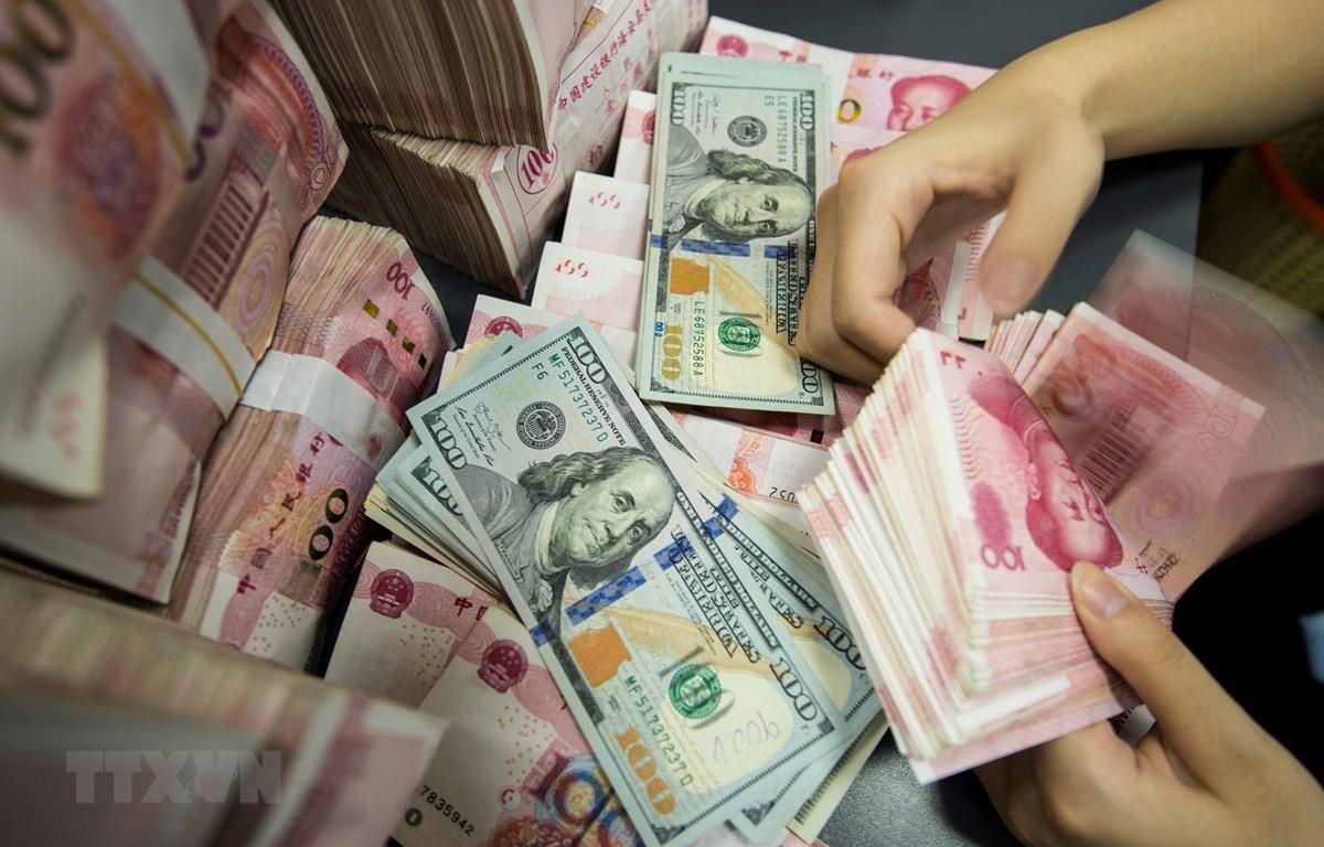 Kiểm đồng 100 Nhân dân tệ tại một ngân hàng ở tỉnh Giang Tô, Trung Quốc. (Ảnh: AFP/TTXVN)