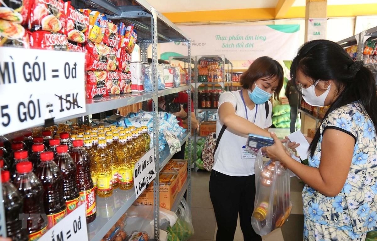 Các tình nguyện viên hỗ trợ người nghèo, người khuyết tật bị ảnh hưởng bởi dịch bệnh COVID-19 mua sắm miễn phí tại siêu thị hạnh phúc 0 đồng. (Ảnh: Thanh Vũ/TTXVN)