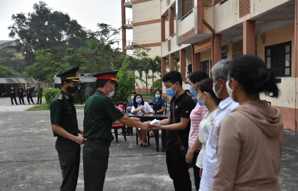 Cán bộ chiến sỹ trao Giấy chứng nhận hoàn thành thời gian cách ly cho người dân. (Ảnh: Mai Trang/TTXVN)