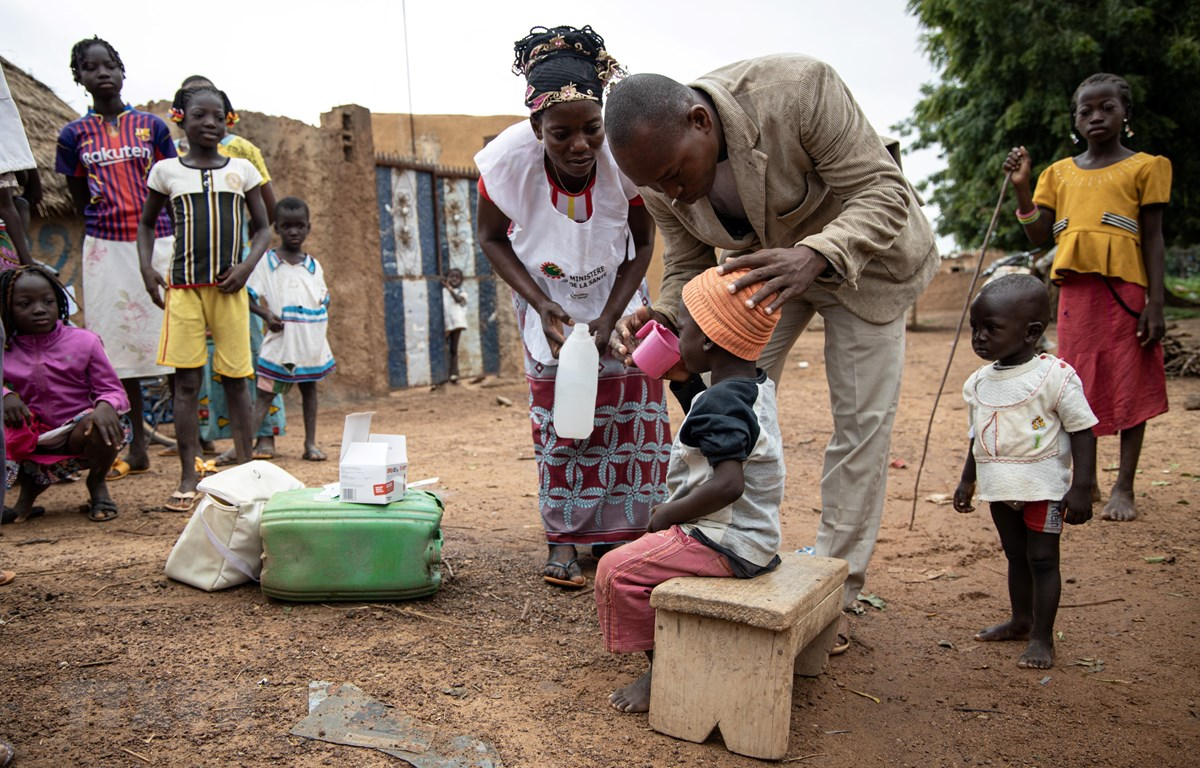 Nhân viên y tế cộng đồng giúp người dân uống thuốc phòng căn bệnh sốt rét tại Ouagadougou, Burkina Faso, ngày 20/8/2019. (Ảnh: AFP/TTXVN)