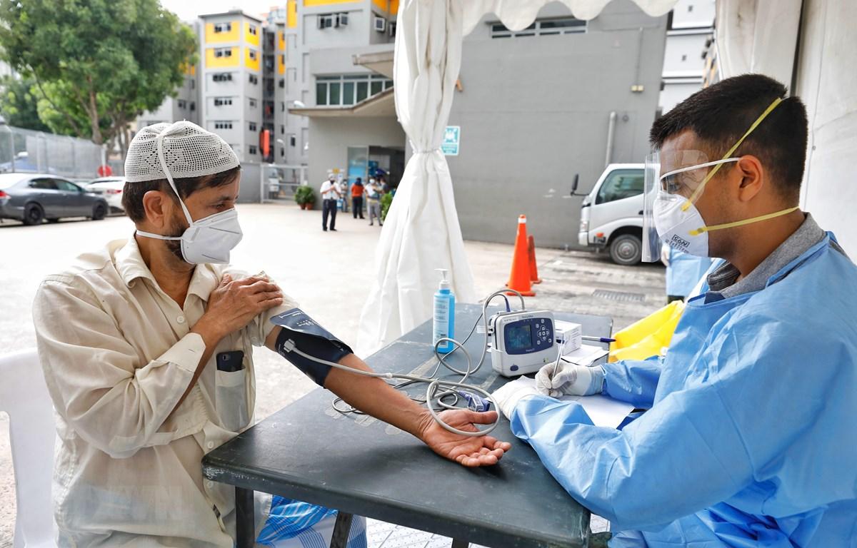 Nhân viên y tế kiểm tra sức khỏe cho người lao động nhập cư tại khu ký túc xá Toh Guan, Singapore ngày 8/4/2020. (Ảnh: THX/TTXVN)
