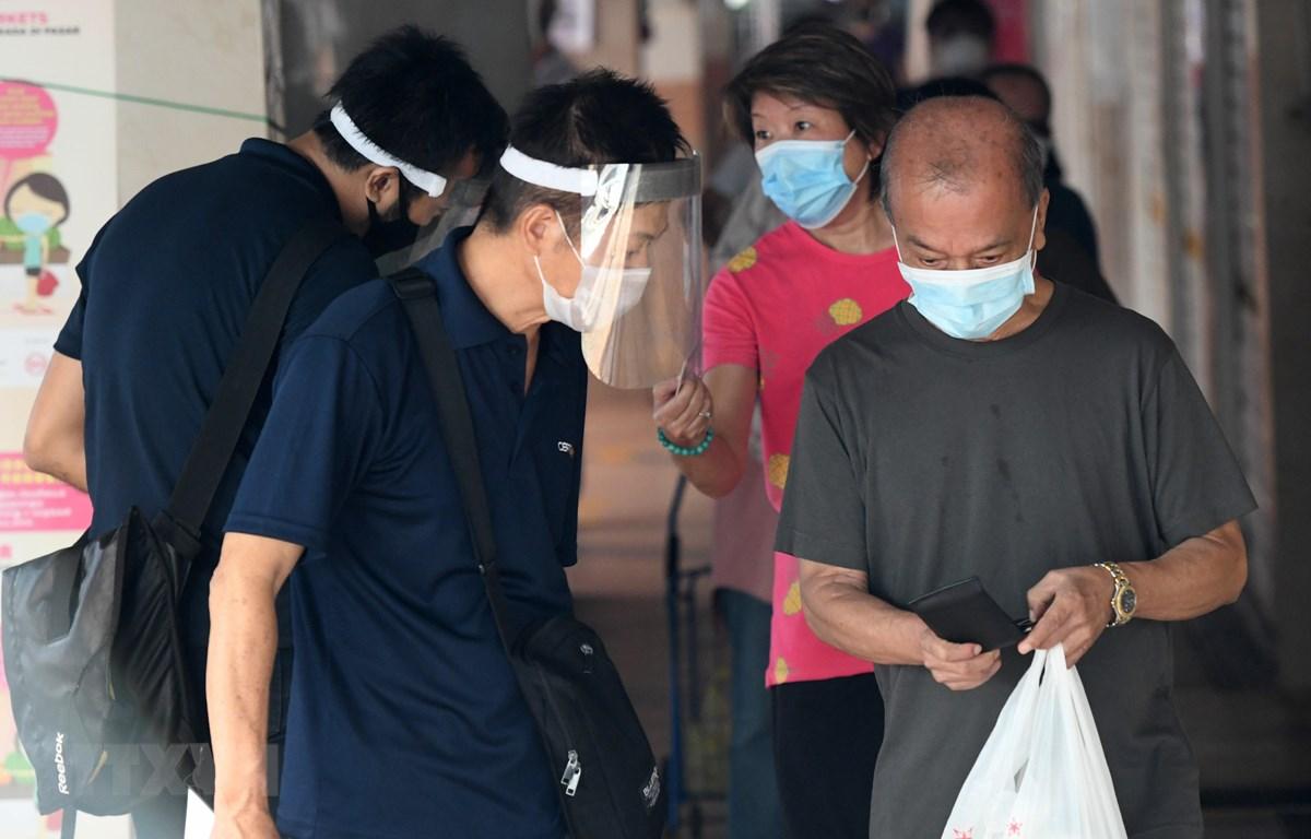Người dân đeo khẩu trang phòng lây nhiễm COVID-19 tại Singapore, ngày 22/4/2020. (Ảnh: AFP/TTXVN)