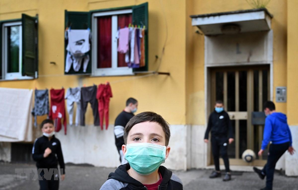 Trẻ em đeo khẩu trang khi chơi trước cửa nhà ở San Basilio, Rome, Italy ngày 18/4/2020 trong bối cảnh dịch COVID-19 đang hoành hành. (Ảnh: AFP/TTXVN)